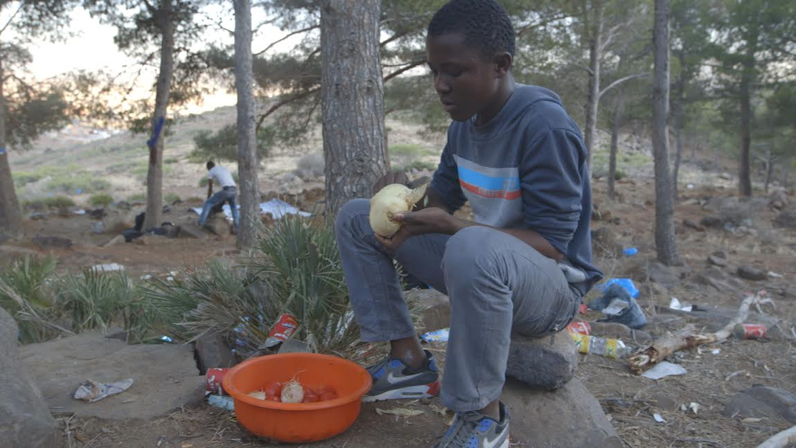 Beni, 14, helps to prepare his brotherhood's one meal of the day with food they have salvaged from the trash. (Isabella Alexander)