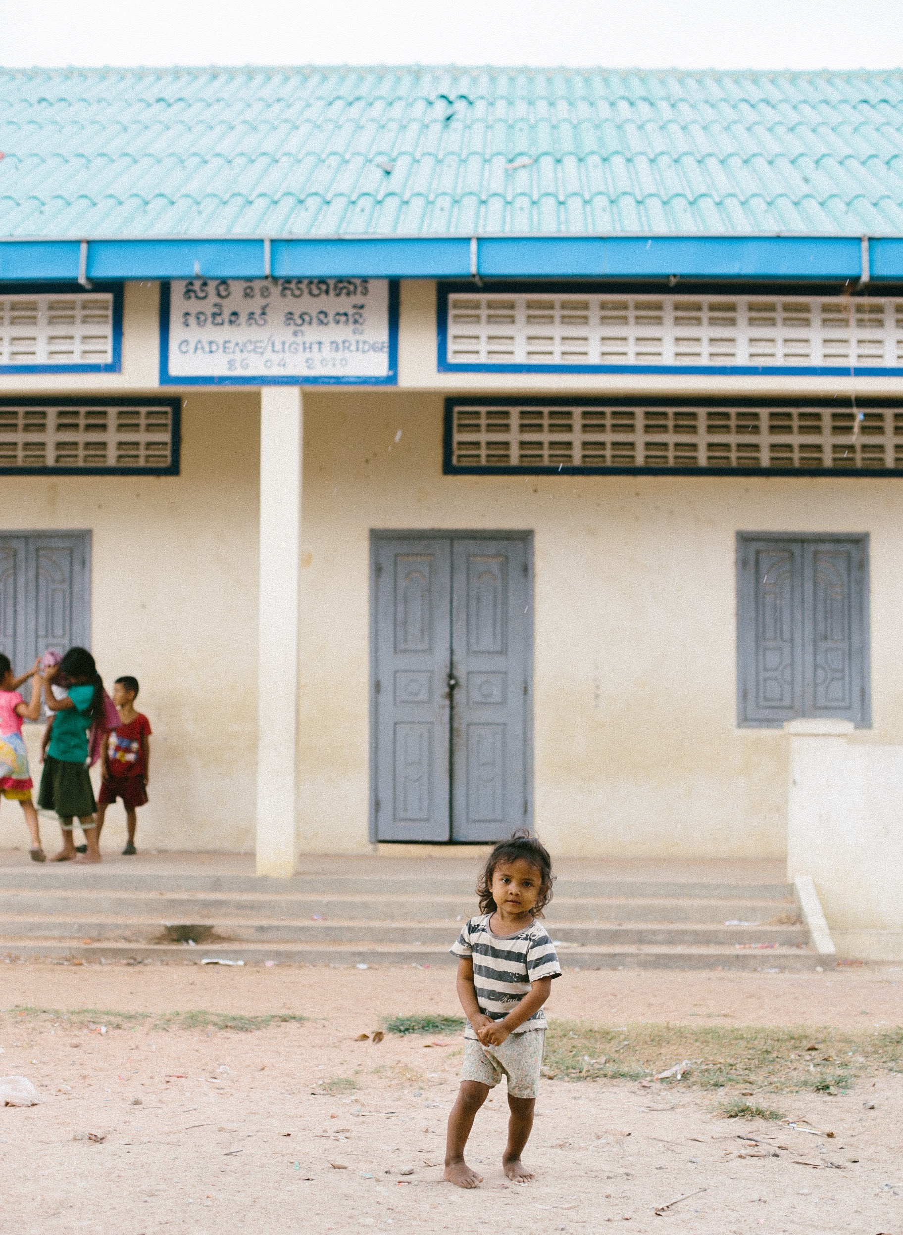 One of the sweetie-pies in front of the current school building...she will begin school in the next year or two!