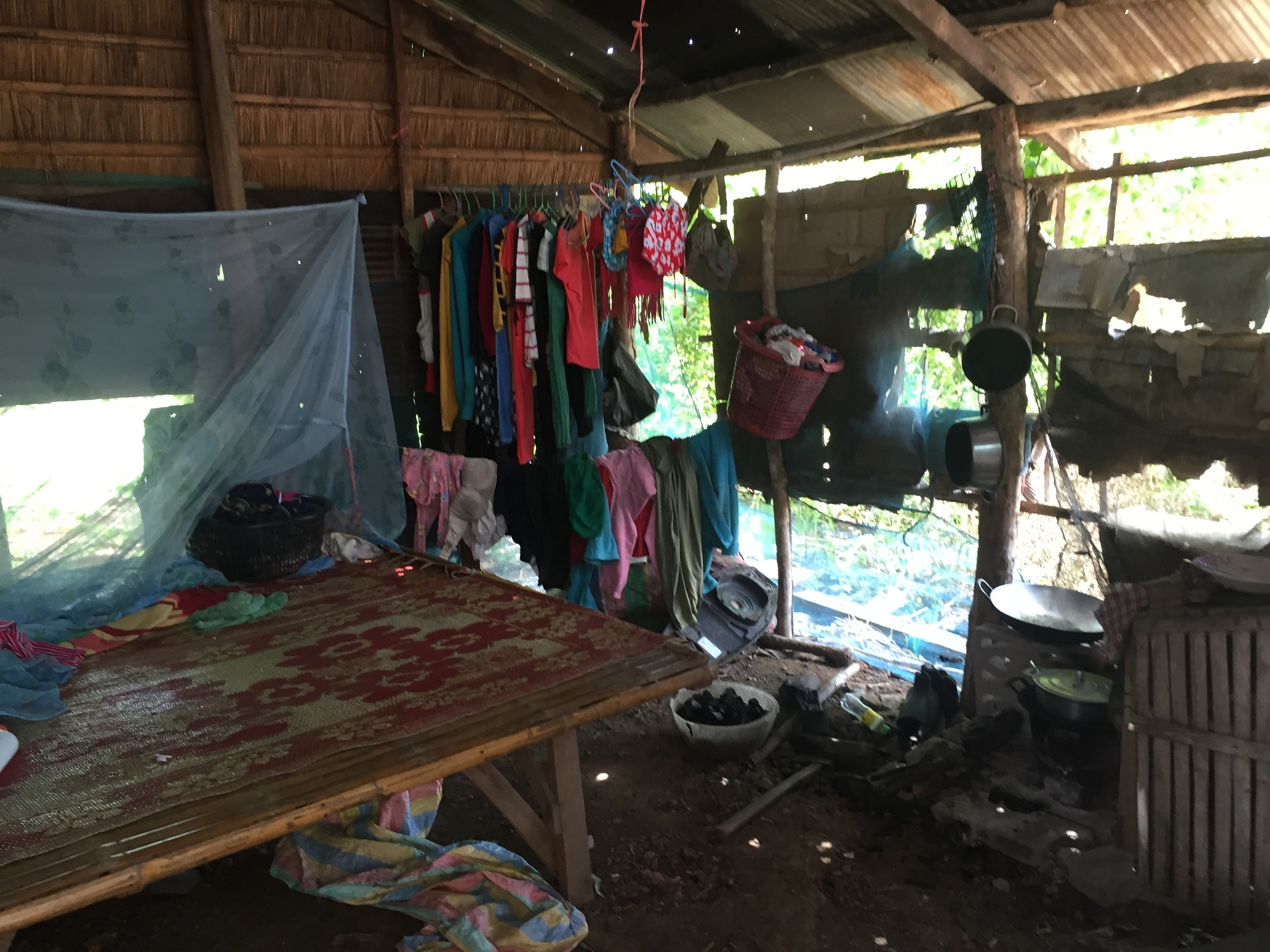Inside Pai's hut and the raised bed she and her daughter share.