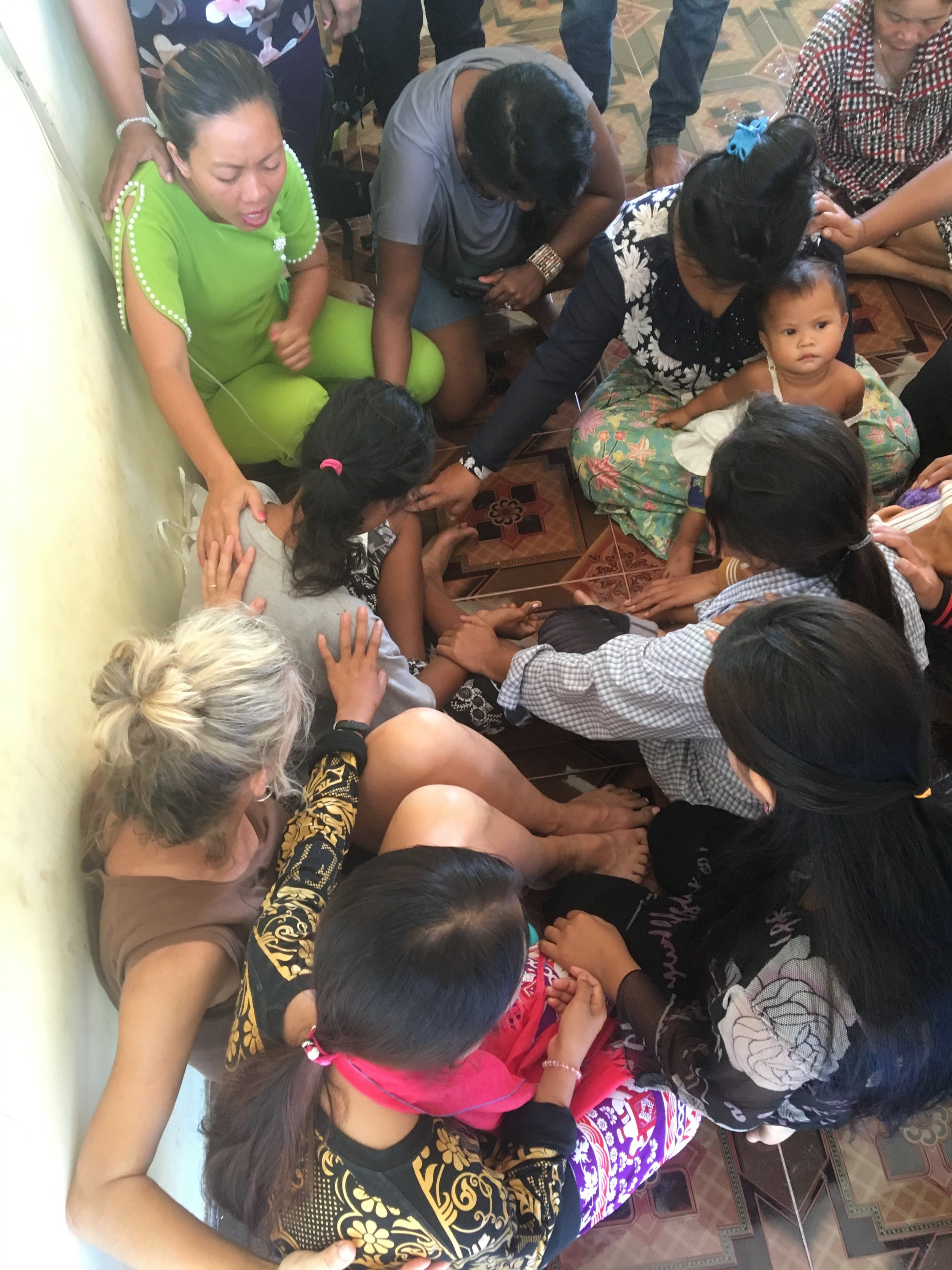 Here are our Landmine Design women praying and laying hands on sweet Chan who was very sick and carried an IV to work with her.  The power of prayer at work among the sweetest village ladies!  Oh, and Jesus healed her!