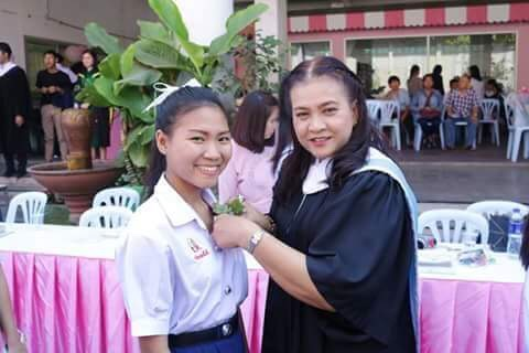 Tiwagorn and a teacher pinning on her corsage