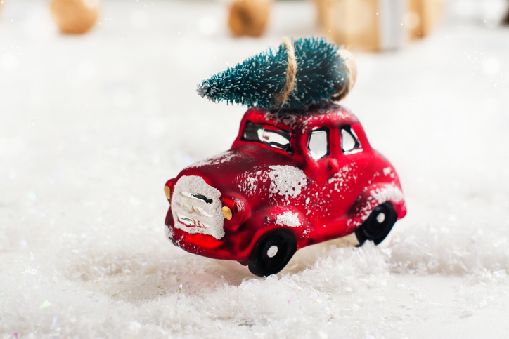 Miniature-red-car-carrying-fir-tree-on-Christmas-background-848695622_727x484.jpeg