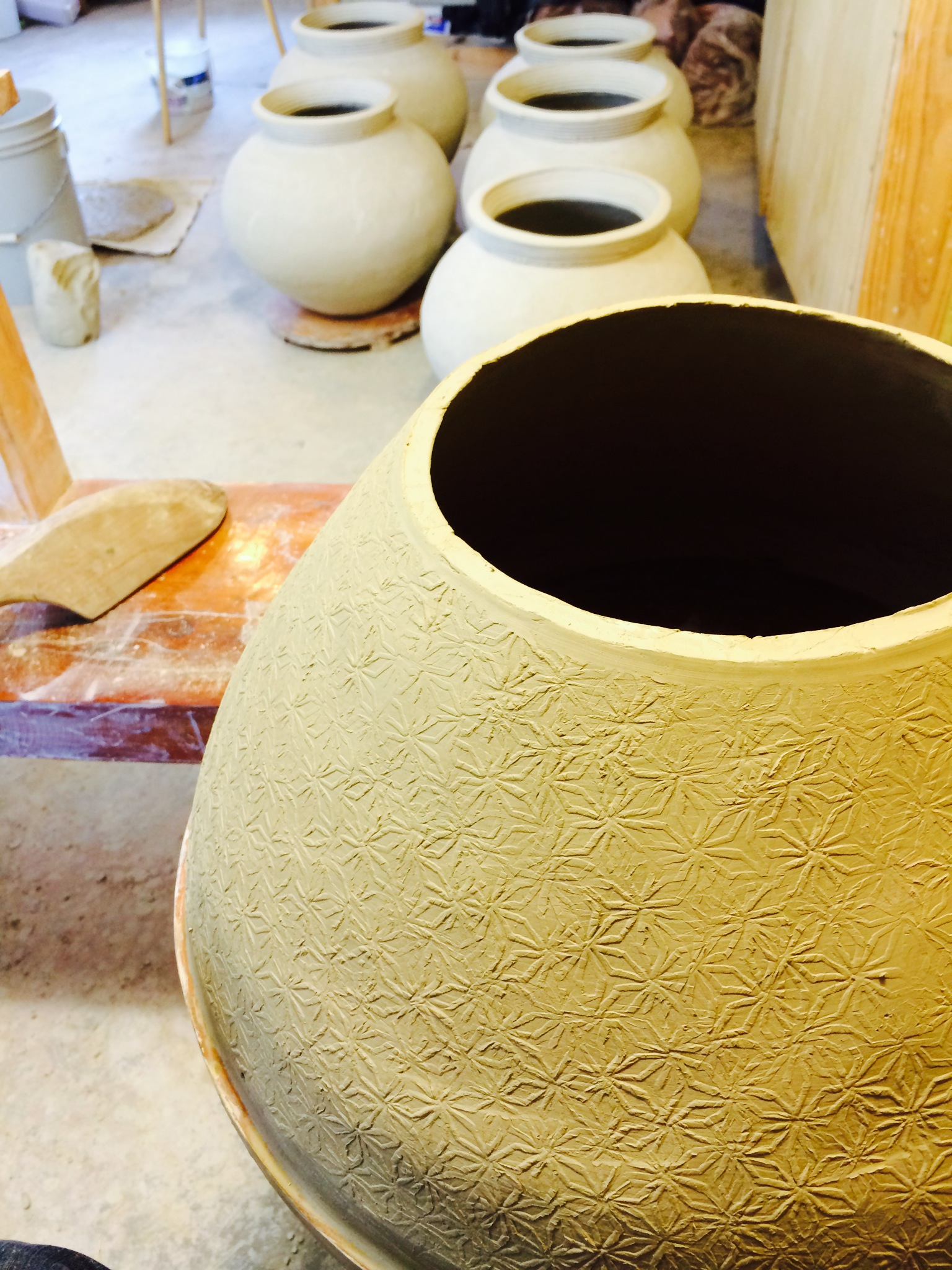 This is what it looks like when I begin.  I start by making the bottom half of the jar first, beginning in the middle of the form. I first build a large cone shaped form with coils. Then the profile is shaped and struck with a textured paddle to further refine the profile and make the walls thinner and more dense.