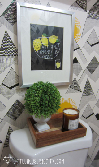 Artwork from Ikea and greenery from Target add life to this wallpapered half bathroom.