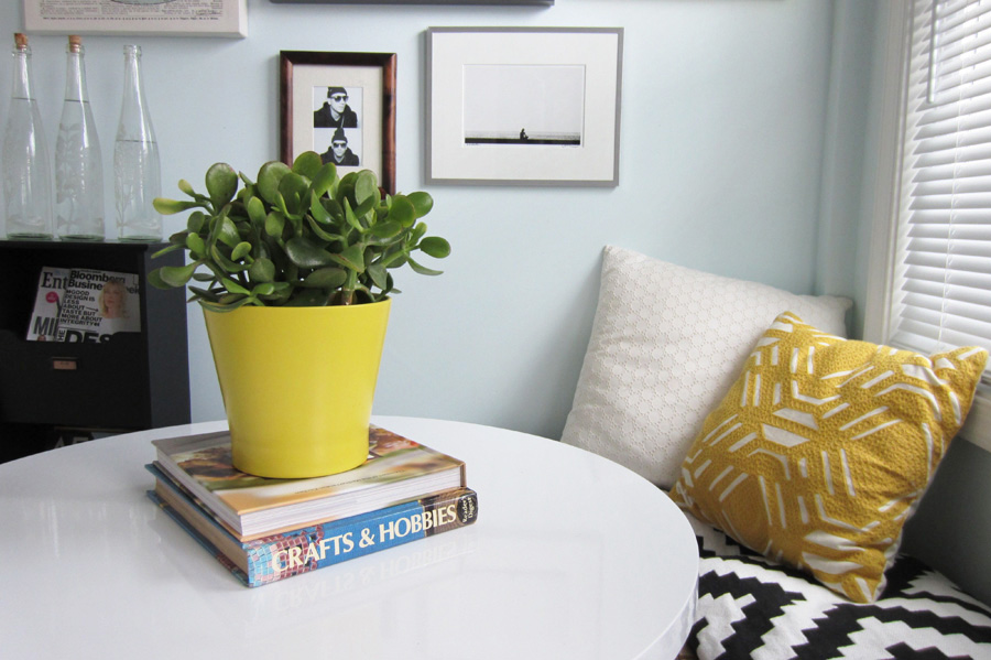 Round white table in breakfast nook with gallery wall in the background