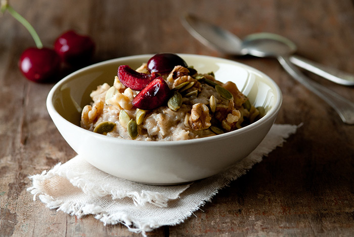 Bowl of Fresh Oatmeal with Pumpkin Seeds, Walnuts and Cherries Food Stock Photo