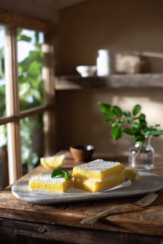 Lemon Bars on a Rustic Farmhouse Table in the Kitchen Stock Food Photo