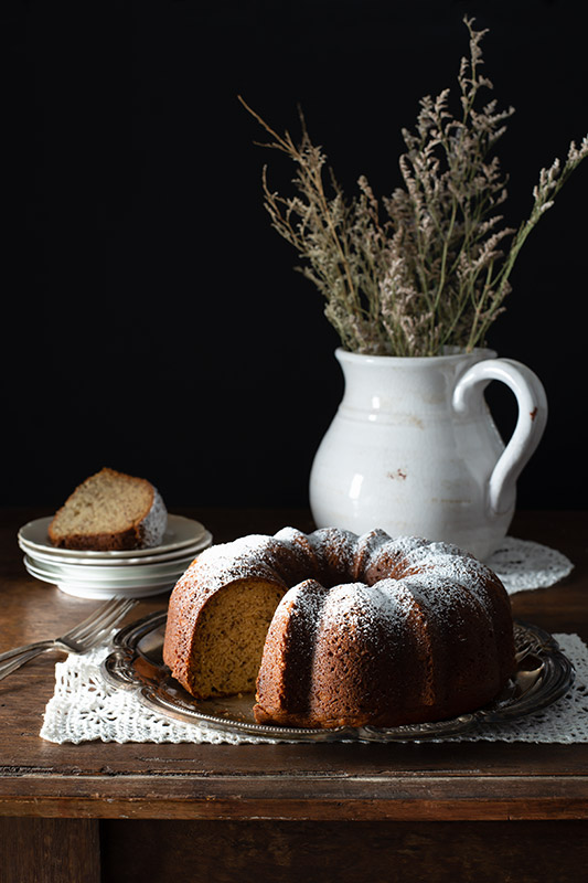 Bundt Cake on a Rustic Farmhouse Table with a Missing Slice in a Dark and Somber Setting Stock Food Photo