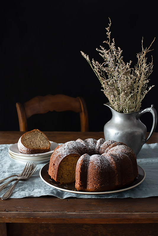 Large Bundt Cake on a Rustic Farmhouse Table with a Missing Slice in a Dark and Somber Setting Stock Food Photo