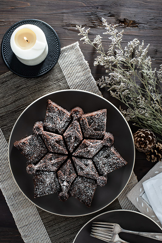 Snowflake Chocolate Cake with a Candle and Pine Cones Stock Food Photo