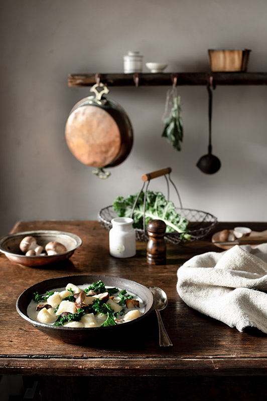 Gnocchi Soup with Mushrooms and Kale in a Rustic Farmhouse Kitchen Stock Food Photo