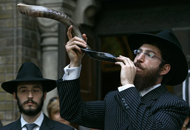 Chabad Rabbi Motti Seligson, left, watches Chabad Rabbi Saadya Notik, from New York blow the shofar, a ram's horn, as a call for spiritual preparation for Rosh Hashana, the Jewish New Year, in front of synagogue in Novi Sad, some 80 kms (50 miles) north of Belgrade, Sunday, Sept. 2, 2007, as a part of marking European Day of Jewish Culture. The shofar is being blown here for the first time since the 1942 Holocaust of over 800 members of the Jewish community in Vojvodina province. New York Rabbis are visiting countries of the former Yugoslavia as a part of Chabad-Lubavitch's global Jewish enrichment program. Rosh Hashana this year starts on the evening of September 12. (AP Photo/Srdjan Ilic)