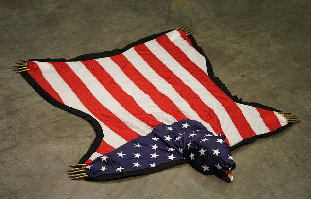 The American Dream Is Alie And Well. Nicholas Galanin. US Flag, felt, .50 Cal Ammunition, Foam, Gold Leaf, Plastic. 2012