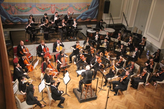 The Aaron Copland School of Music orchestra under the baton of Maestro Peress, in the historic ballroom of the Bohemian National Hall.