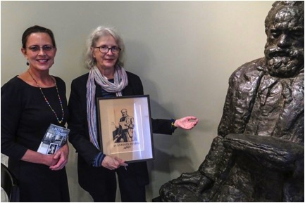 Golden Alley Press Editor Nancy Sayre and DAHA Board Member Majda Kallab Whitaker display book  The House of Prague  and etching of Dvořák next to statue by Ivan Mestrovic in  Dvořák Room.  Photo courtesy of Czech Center New York.