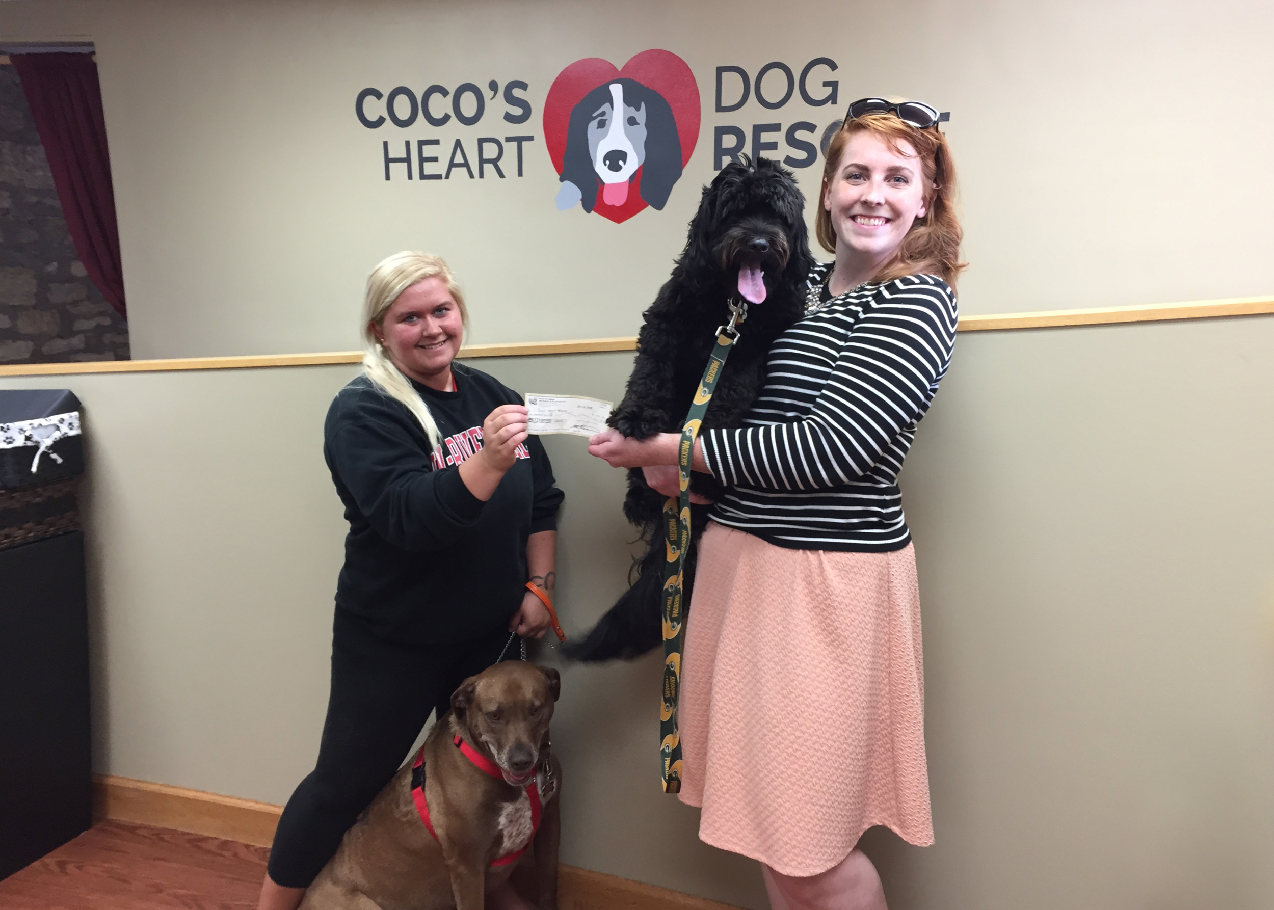 NP Design & Photography Graphic Designer, Kelly, with her adopted dog from Coco's Heart, Melvin, presenting a check for $1000 to CHDR Volunteer, JoHanna.