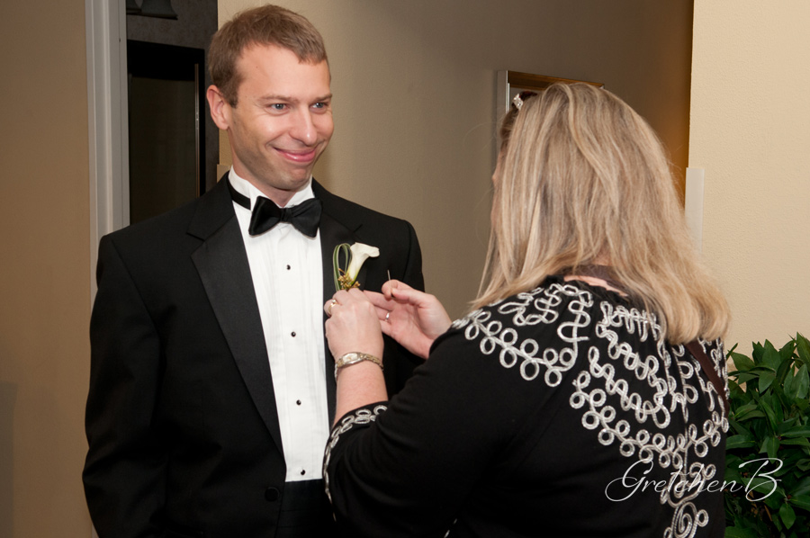 Rachael Grammer with  Two Hearts Weddings  pins on a boutonniere for a groom.  Thank goodness she was there, because the default person when there is not a planner is the photographer/videographer.  Scary. Photo courtesy of  Gretchen B Photography .