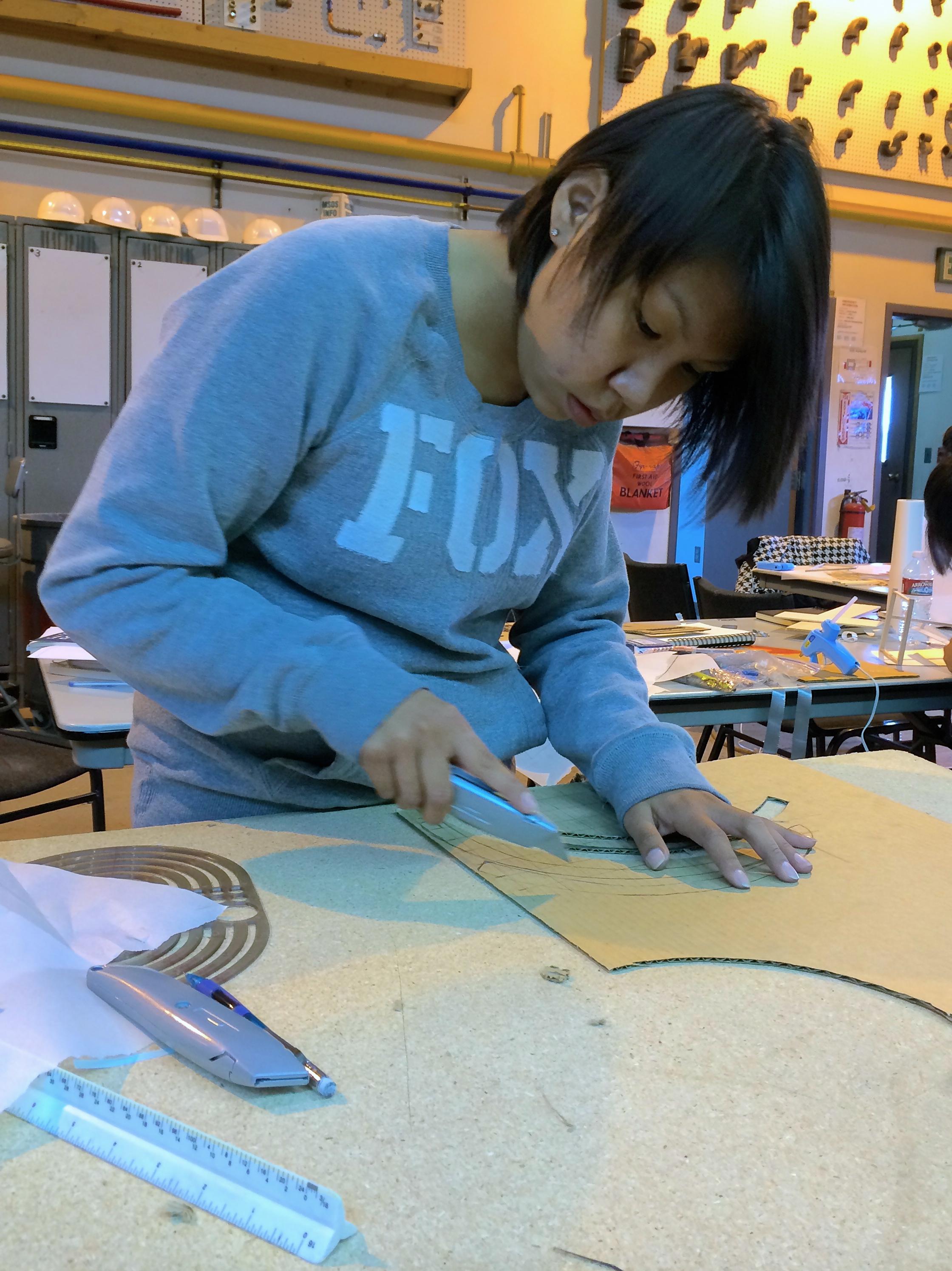 Marina cuts structural ribs from cardboard.
