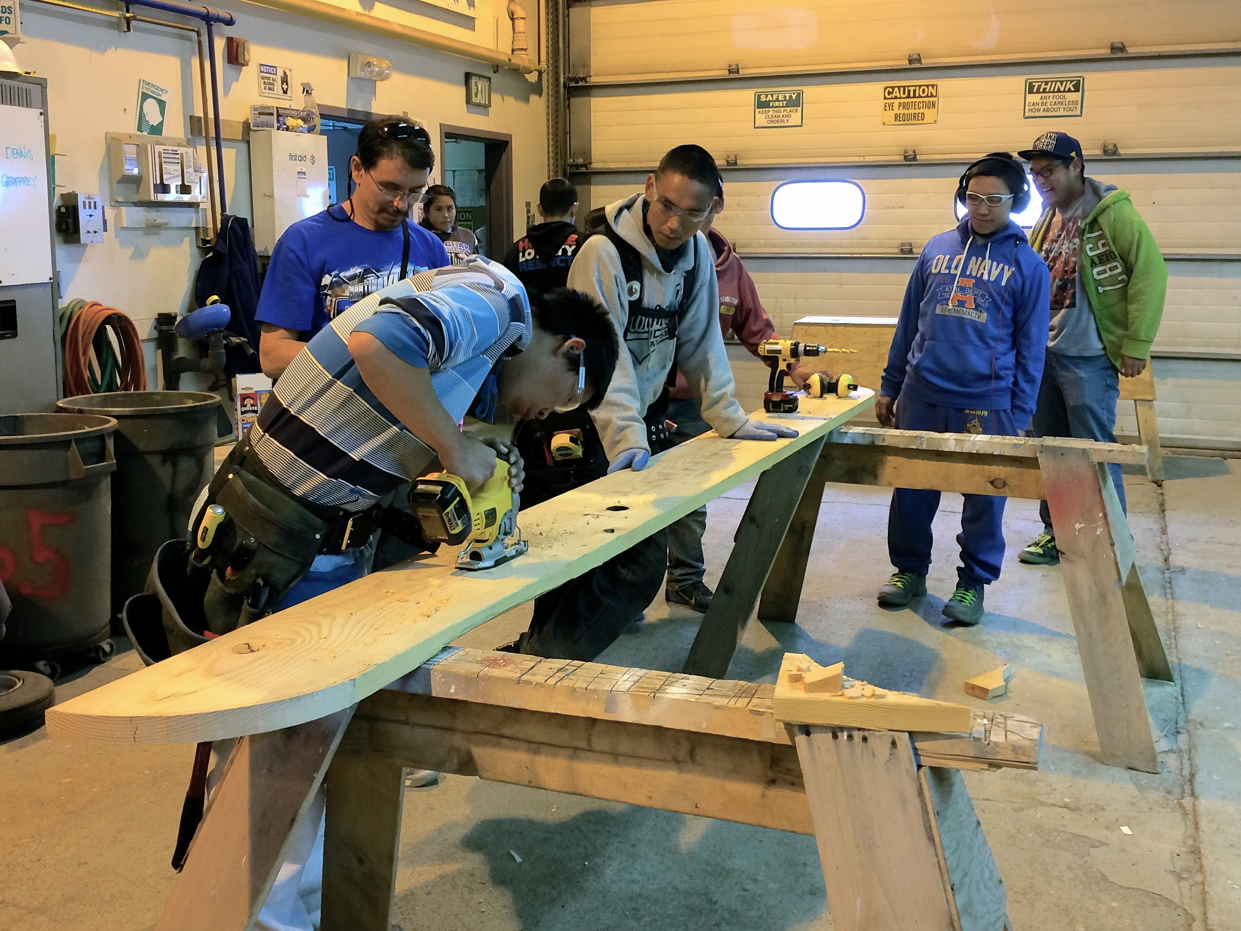 Dennis using a jig saw to cut holes for a forklift in the first ski, while Rob, Anu, Billy, and Mike O. look on.