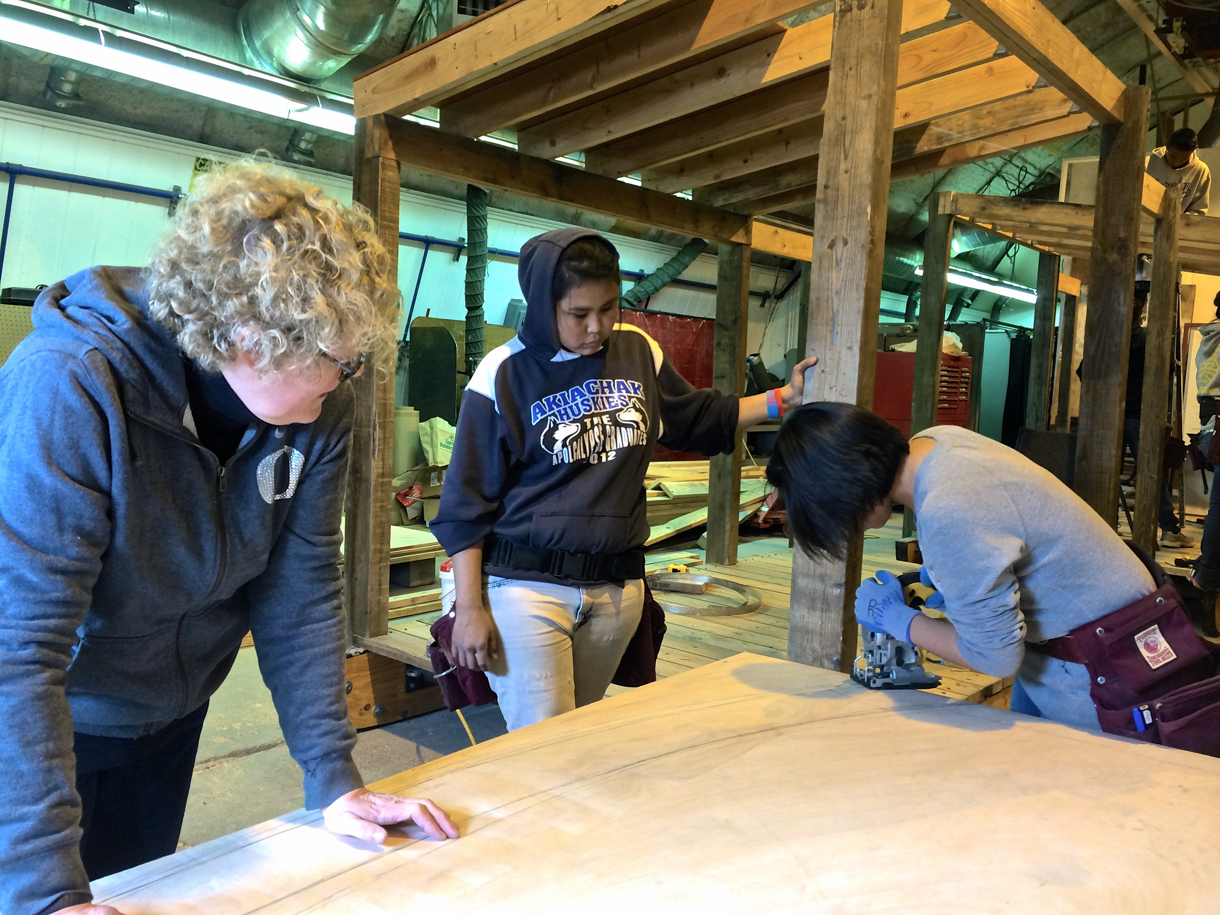 Milly and April look on while Marina cuts along their curved rafter lines.