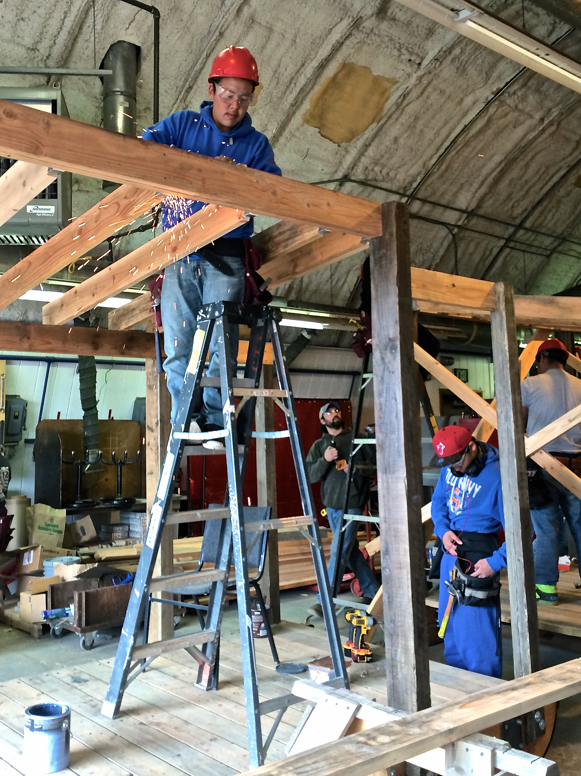 Geoffrey grinds off the tops of the joist hangers, since the only ones available were too long for our beams.