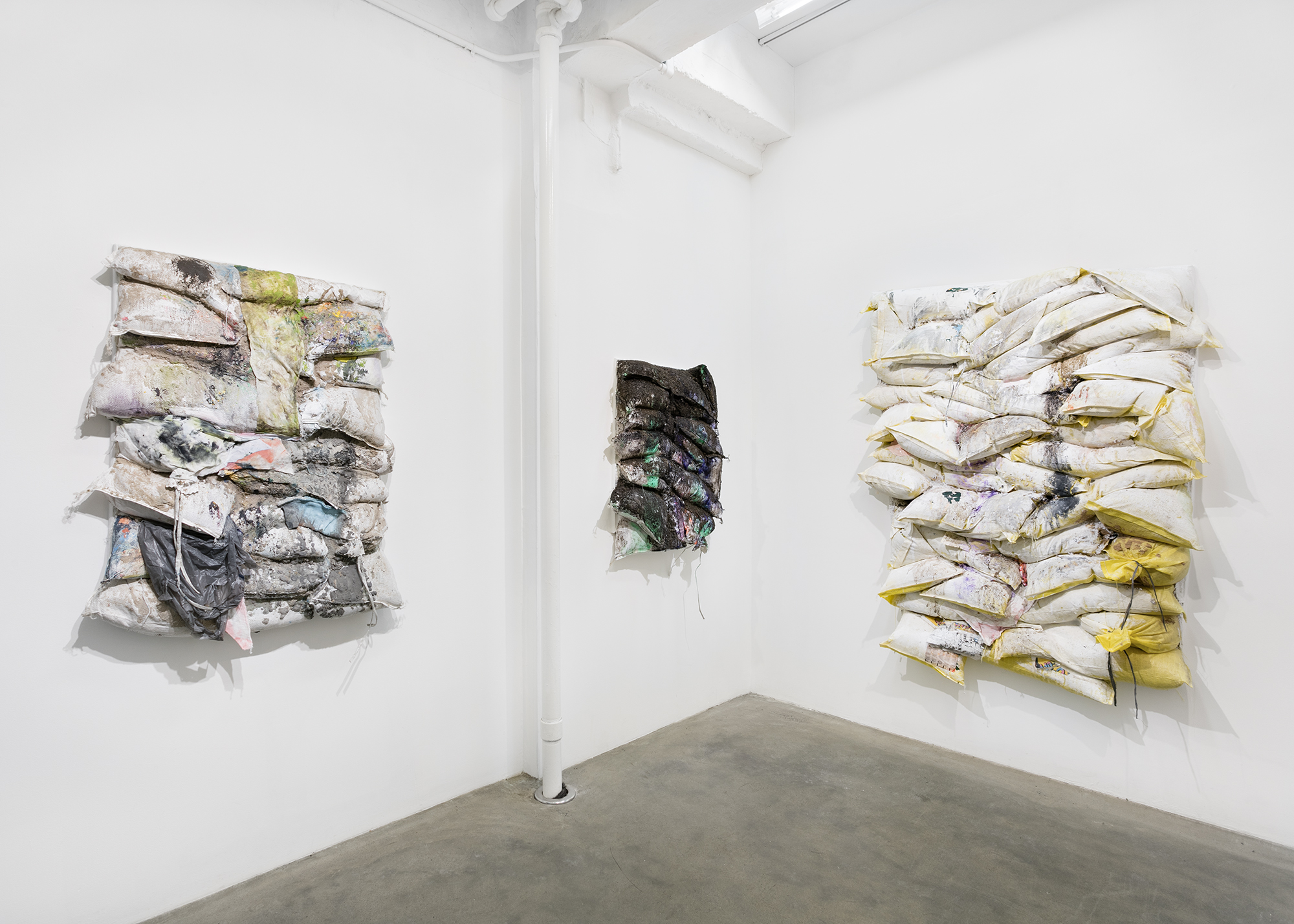 Installation view of Jeremy Lawson 'Rain Follows the Plow' showing works made with assembled and painted found sandbags