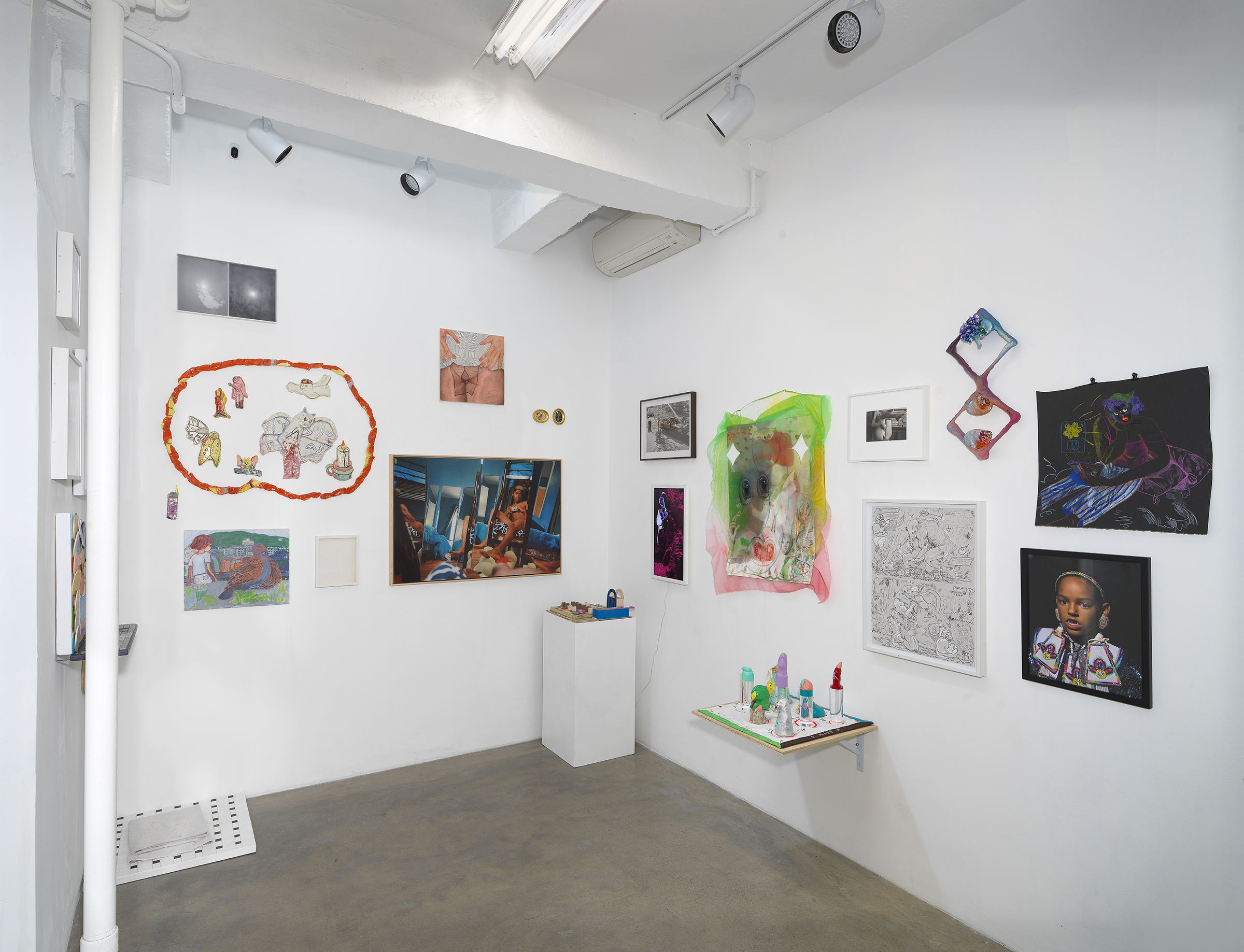 Installation view of 'Can You Dream It' featuring sculptures and salon-style hanging of multimedia works by various artists