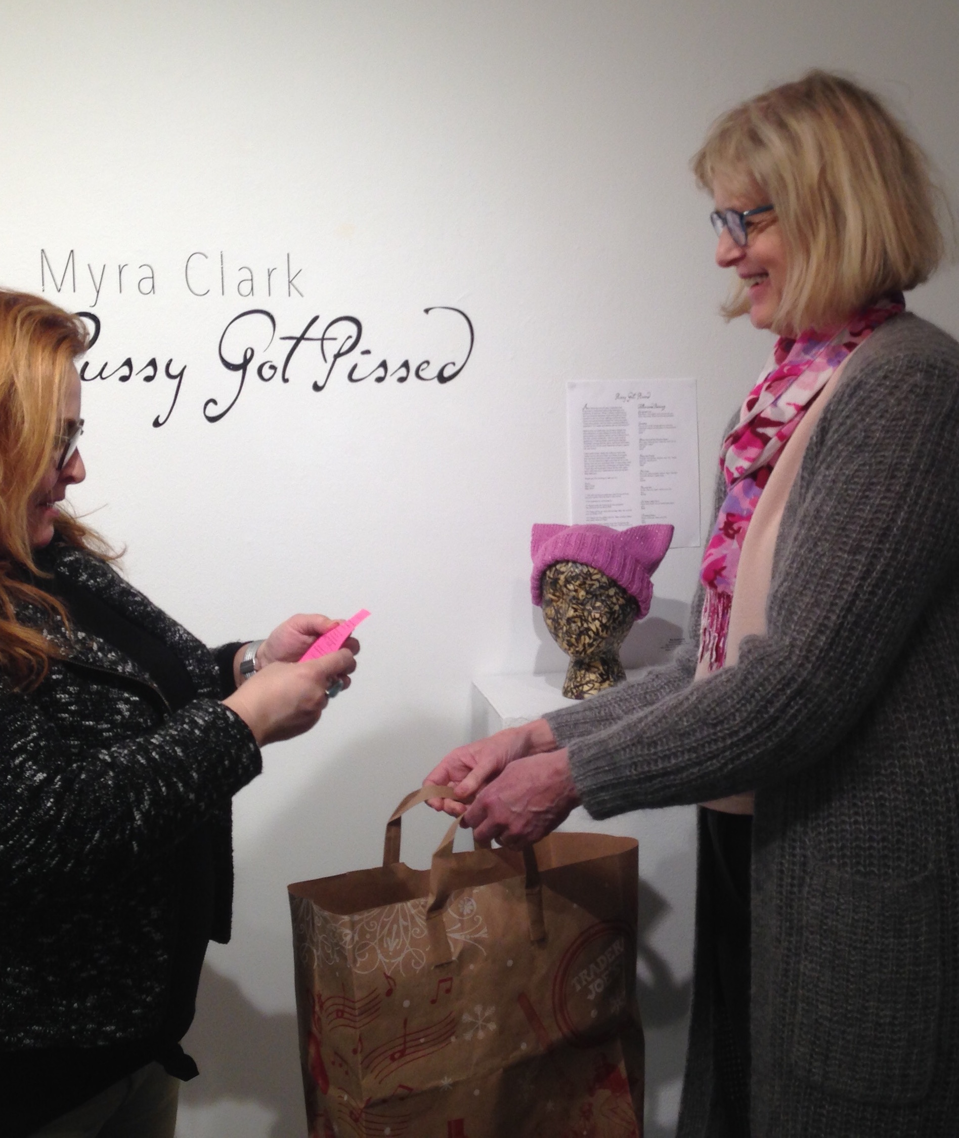 "Lauren Carrera (on left), multi-media and installation artist, reads the name of the pussyhat winner for the show ""Pussy Got Pissed."" Myra Clark, the show's artist, holds the bag of entries for the drawing."
