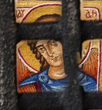 Detail, Narrow Door: hand-embroidered Guardian Angel icon, seen through a speakeasy grille.