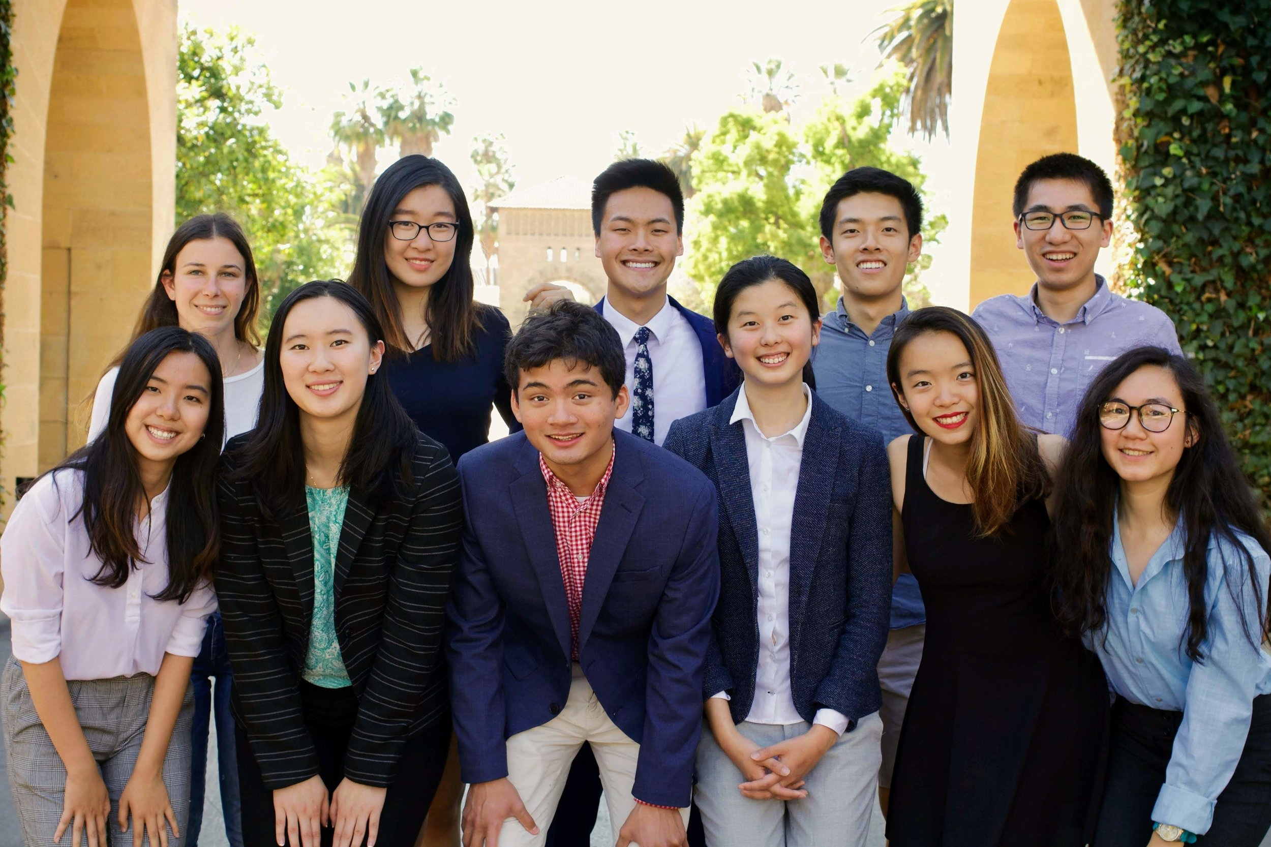 The 2018-19 Stanford FACES Executive Team poses for a collegial photo on Stanford's historic main quad. Pictured from left to right, front row: Zhenqi Hu (Vice President, On-Campus Programming), Caroline Zhang (Vice President, Alumni Relations), Nikhil Shankar (Co-President), Celia Xinuo Chen (Co-President), Victoria Yaqing Yang (Executive Member), Cathy Dao (Vice President, Budget). Back row: Cami Katz (Vice President, Telesummit), Lilian Kong (Outgoing Co-President), Troy Shen (Executive Member), Zecheng Wang (Vice President, Chapter Relations), Yulou Zhou (Executive Member). Not pictured: Andrew Tang (Executive Member), Francesca Lupia (Outgoing Co-President and Executive Member).