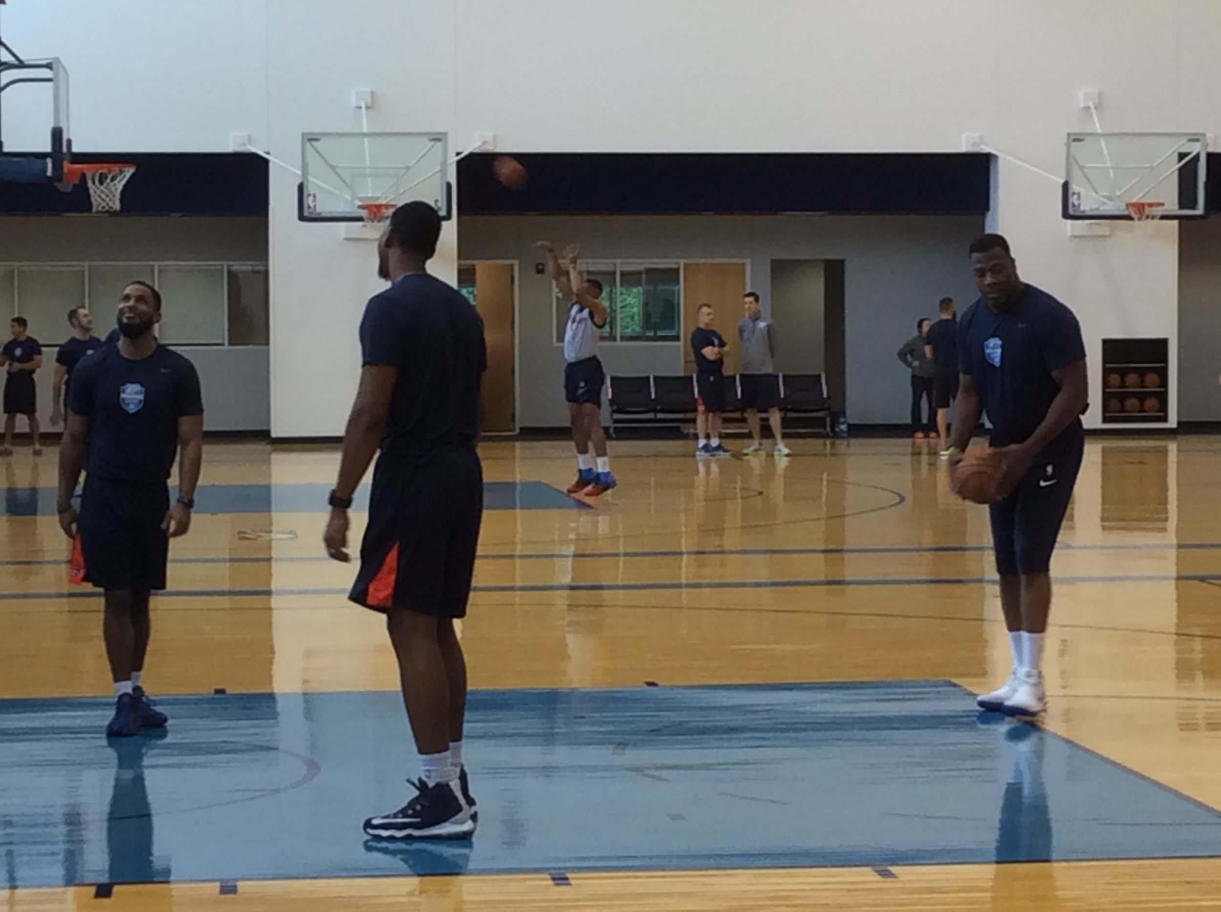Russell Westbrook (background) shoots free throws at the end of Thunder shootaround this morning while head coach Billy Donovan visits with team physician Dr. Donnie Strack at the INTEGRIS Thunder Development Center.