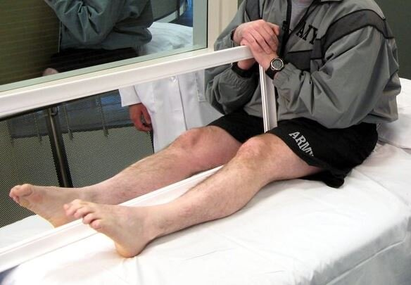 A patient holding a mirror to reflect his intact limb as part of mirror therapy.