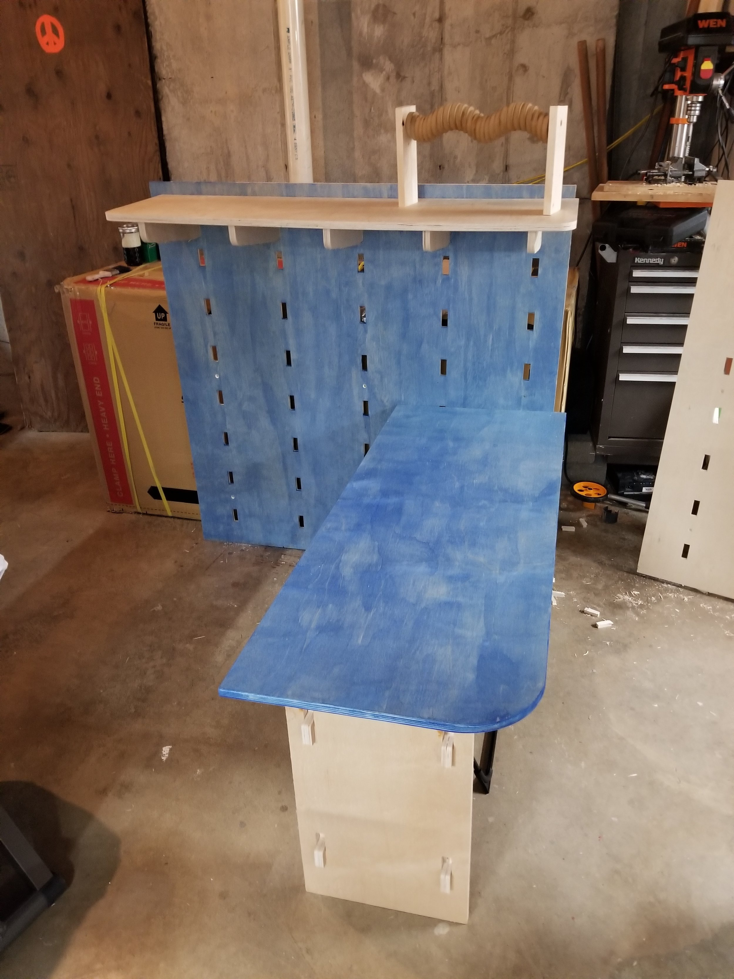 My first table. The table and the wall together costs around $50. I was able to cut 2 shelves and the supports and 5 hooks with several parts still being able to be cut from the same board. It is one .5 inch board and one .75 inch baord.
