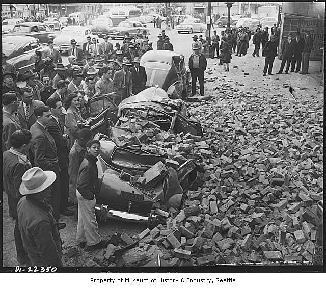 Car_crushed_by_fallen_brick_outside_Busy_Bee_Cafe_after_earthquake_Seattle_April_1949.jpg