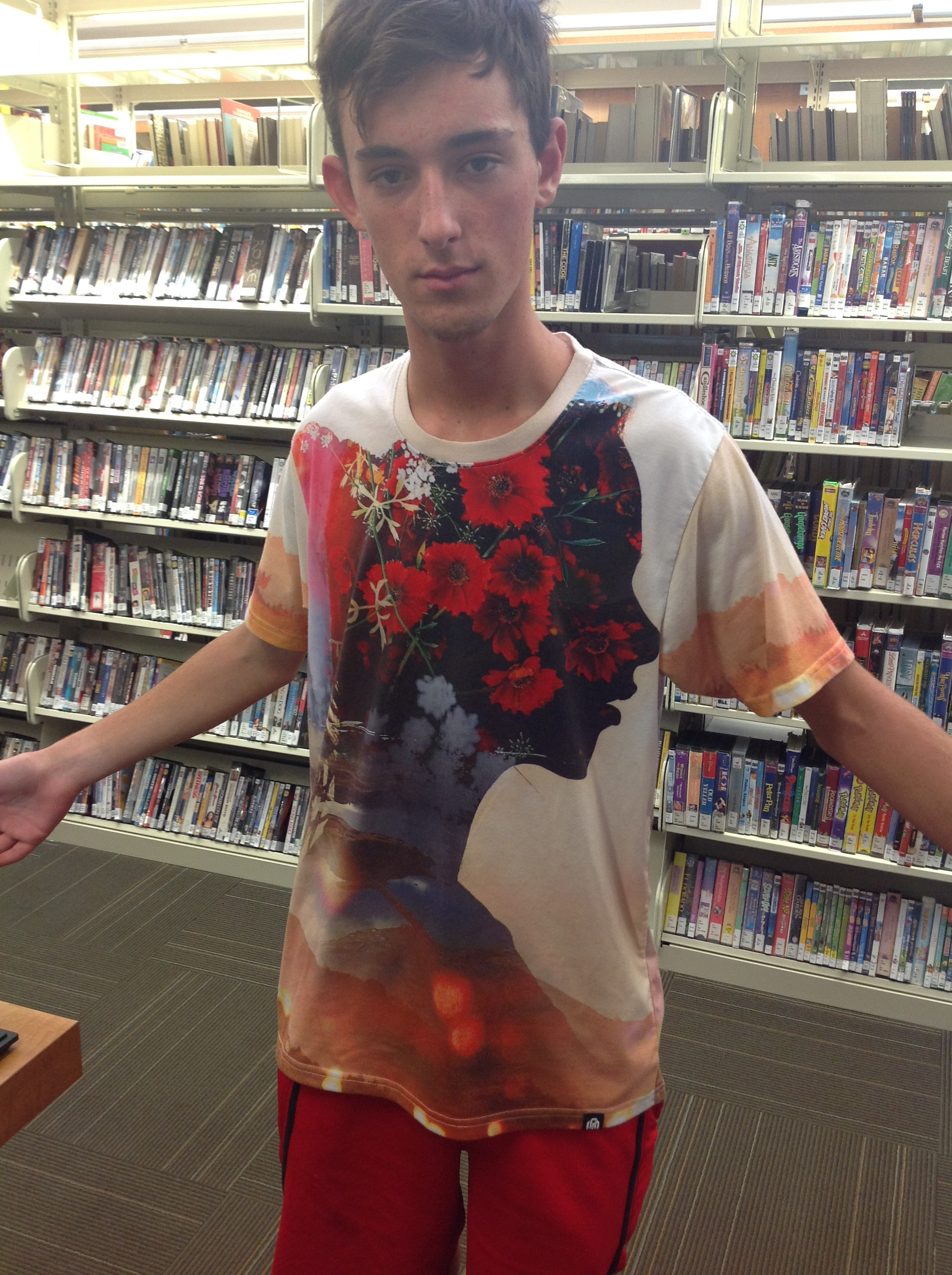 A young man at the library wearing an awesome graphic in Melon and Denim tones with a Coca-Cola graphic feel suitable for #WoodStock50.