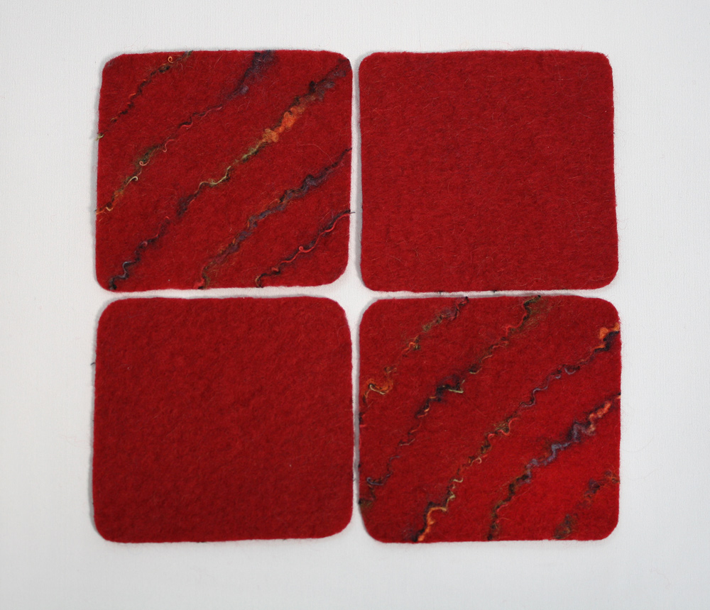 "Rich red, reversible coasters, 4.5"" square(ish), wet-felted coasters.  $29.00.  To purchase, please   contact me !"