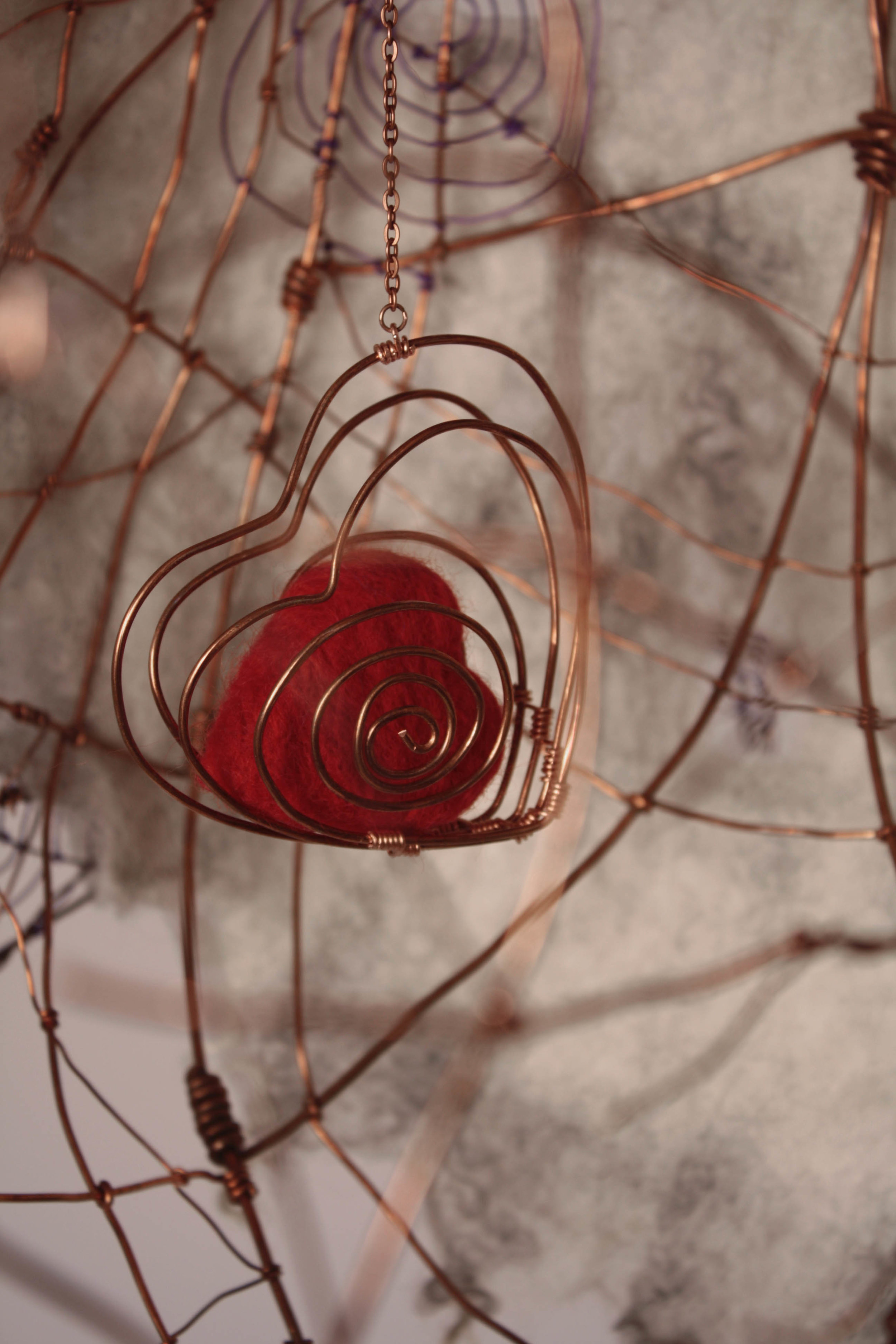 3D felted red heart inside a copper wire heart-shaped cage dangles inside