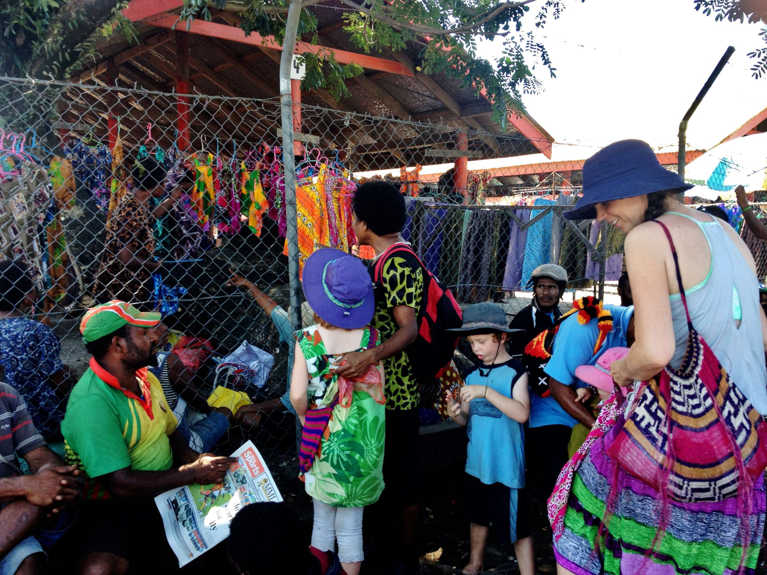 The fence didn't stop Auntie Belinda from buying the girls a meri blaus at the Main Market in Lae while we waited outside for a PMV.