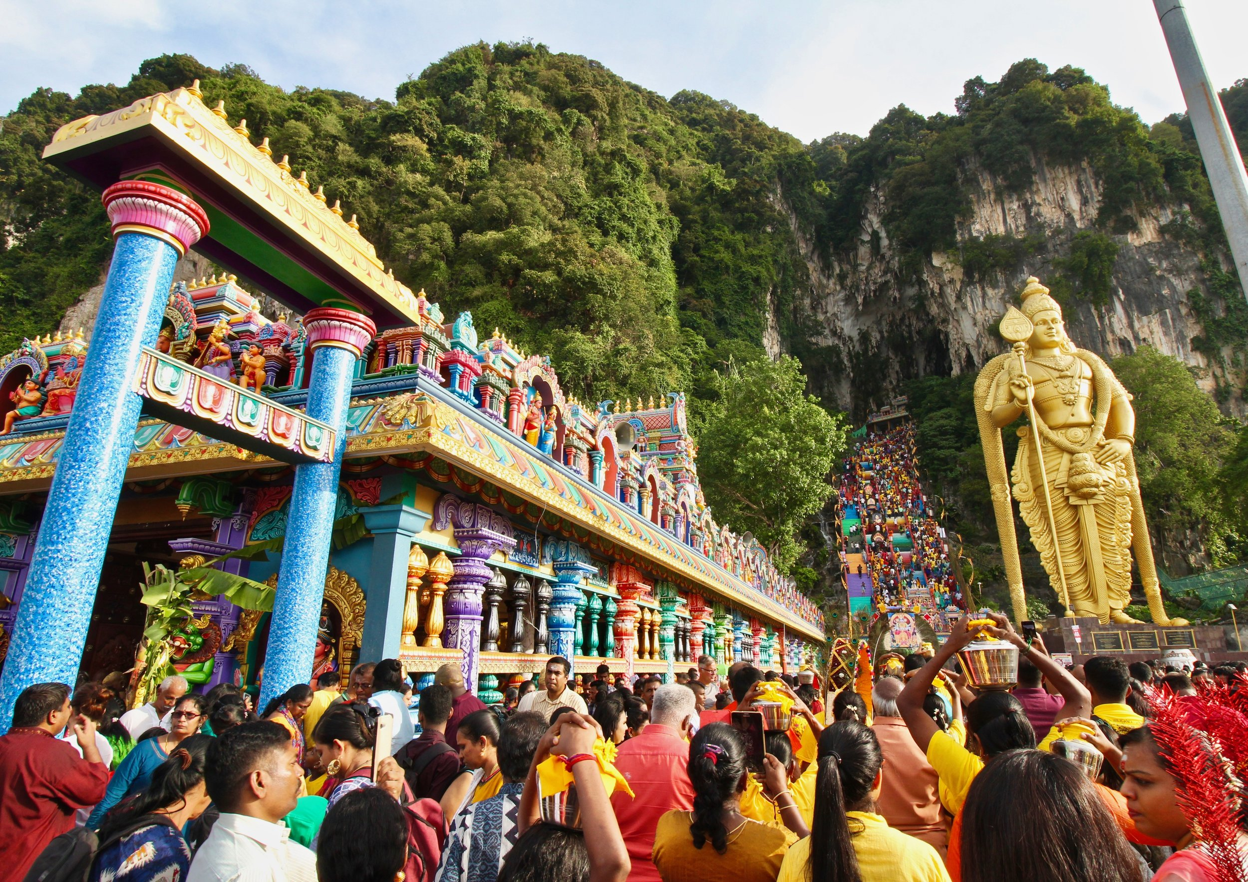 The crowd begins to thicken as it approaches the statue of Lord Murugan, before squeezing tightly through the entrance to the stairs.