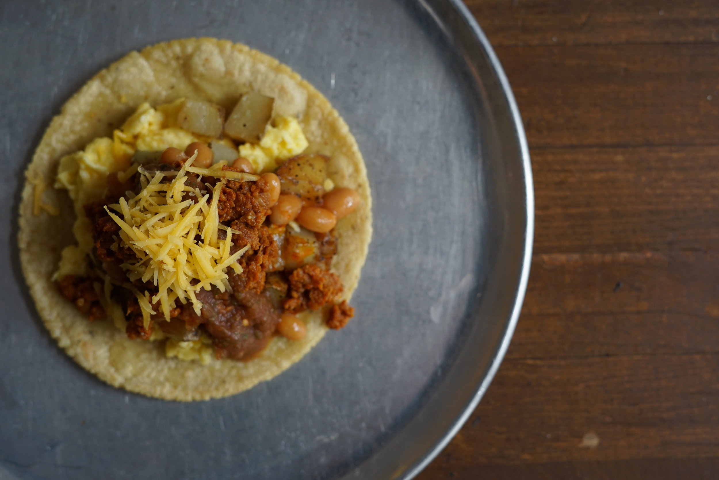 Chorizo con Papas  Mexican Pork Chorizo on top of scrambled eggs, served with potatoes, pork n' beans, salsa and queso amarillo.