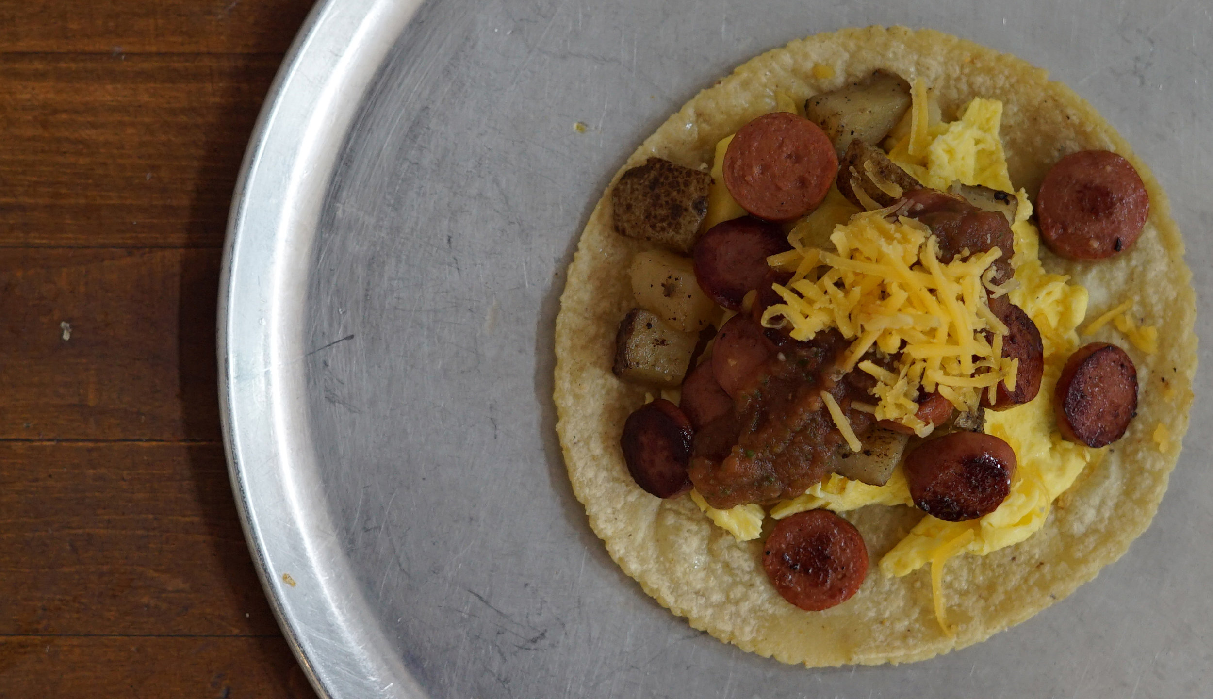 Weenie con Huevo  Weenie and eggs served with salsa potatoes and queso amarillo.