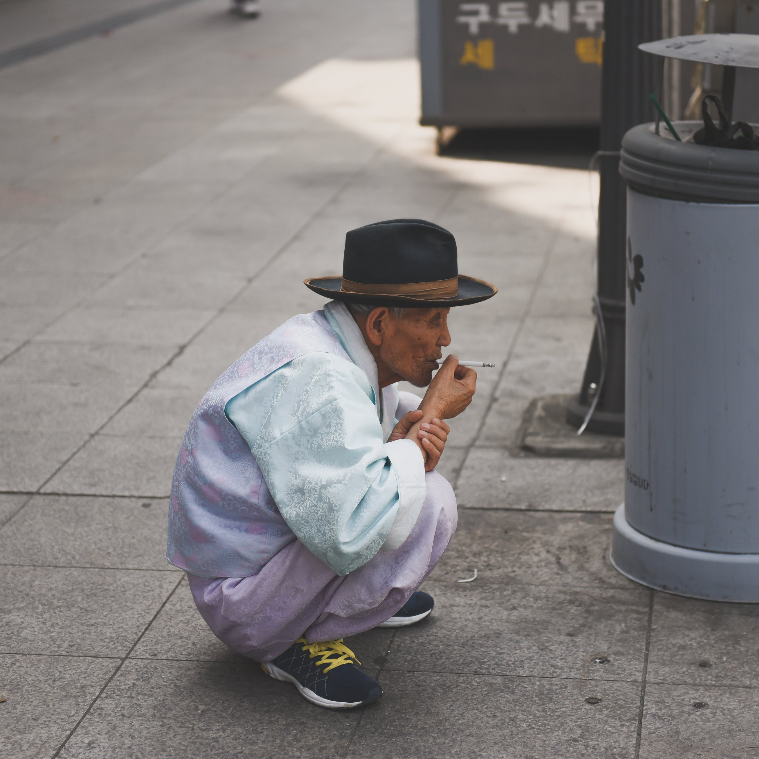 Guy crouching and smoking cig.jpg
