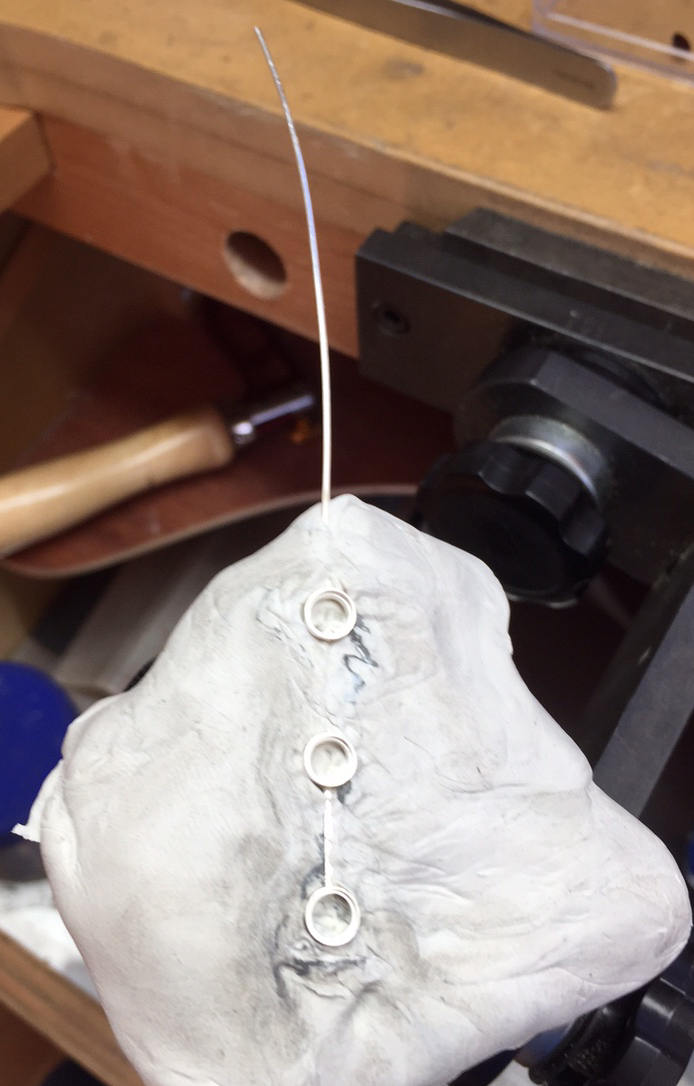 earring embedded into jettset, ready for stone setting.