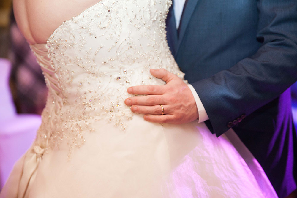 bride-and-groom-first-dance-showing-grooms-wedding-ring-holding-her-waist.jpg
