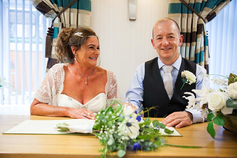 bride-and-groom-just-married-signing-registry-form-at-calderdale-office.jpg