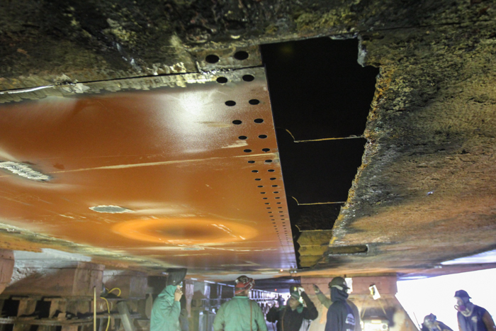 The sized steel plate has been fitted into place on the ship's hull. The butts of the plate are tack welded into place and the seams will be riveted. This arrangement gives the hull more flexibility and strength than an all welded hull.