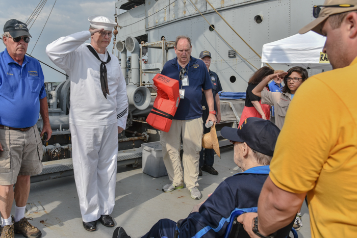 Hugh Cadzow welcomes Richard aboard on behalf of our Armed Guard Unit, accompanied by a group of Boy Scouts. (Don't worry, Ernie just got caught in the pictureon his way to do his routine pre-cruise lifejacket demonstration for the passengers)