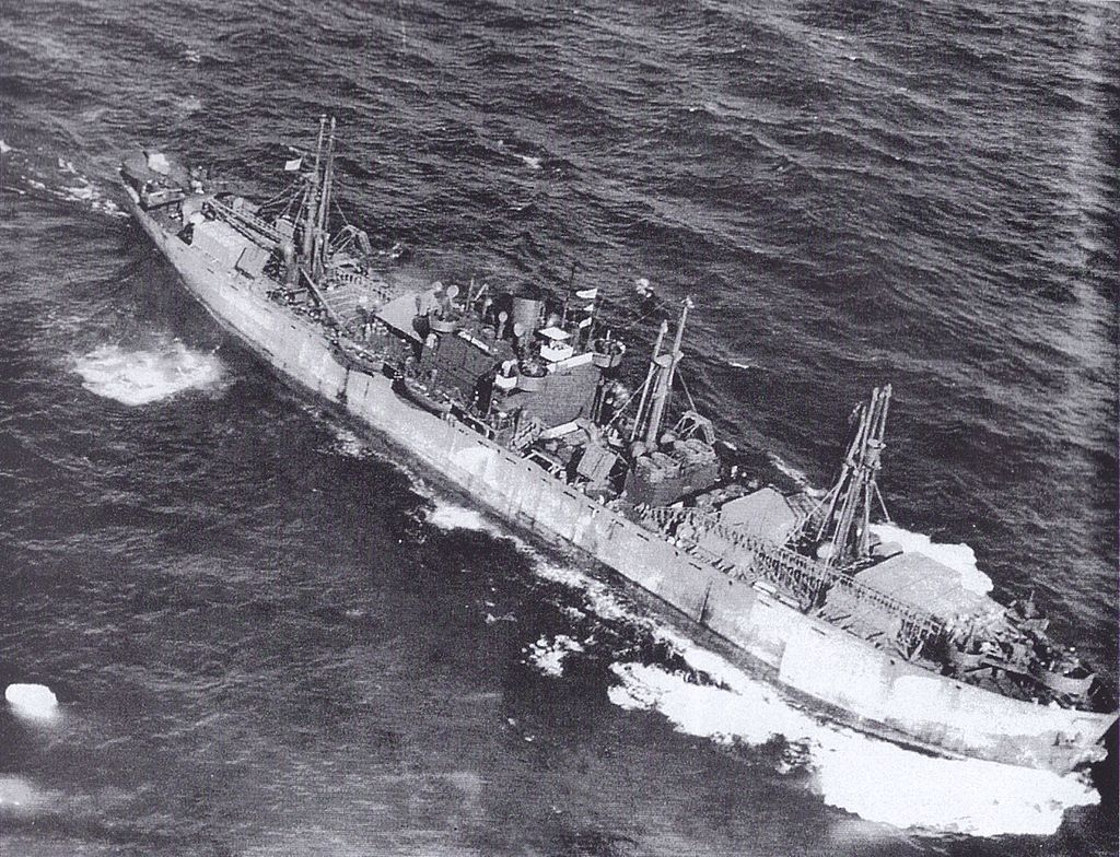 """This aerial photograph of the JOHN W BROWN outbound from the US carried a large deck cargo even after her conversion to a """"Limited Capacity Troopship."""" This shot is most likely taken in the summer of 1943 during her second voyage. Notice how low in the water she is."""