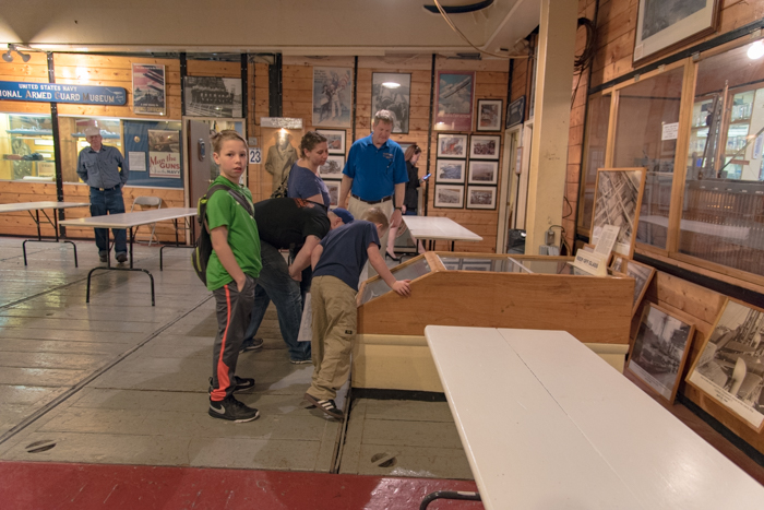 Visitors enjoyed exploring the Tween decks. This family is looking through the window to the lower #2 hold to check out the fully restored truck, plane propeller and howitzer.