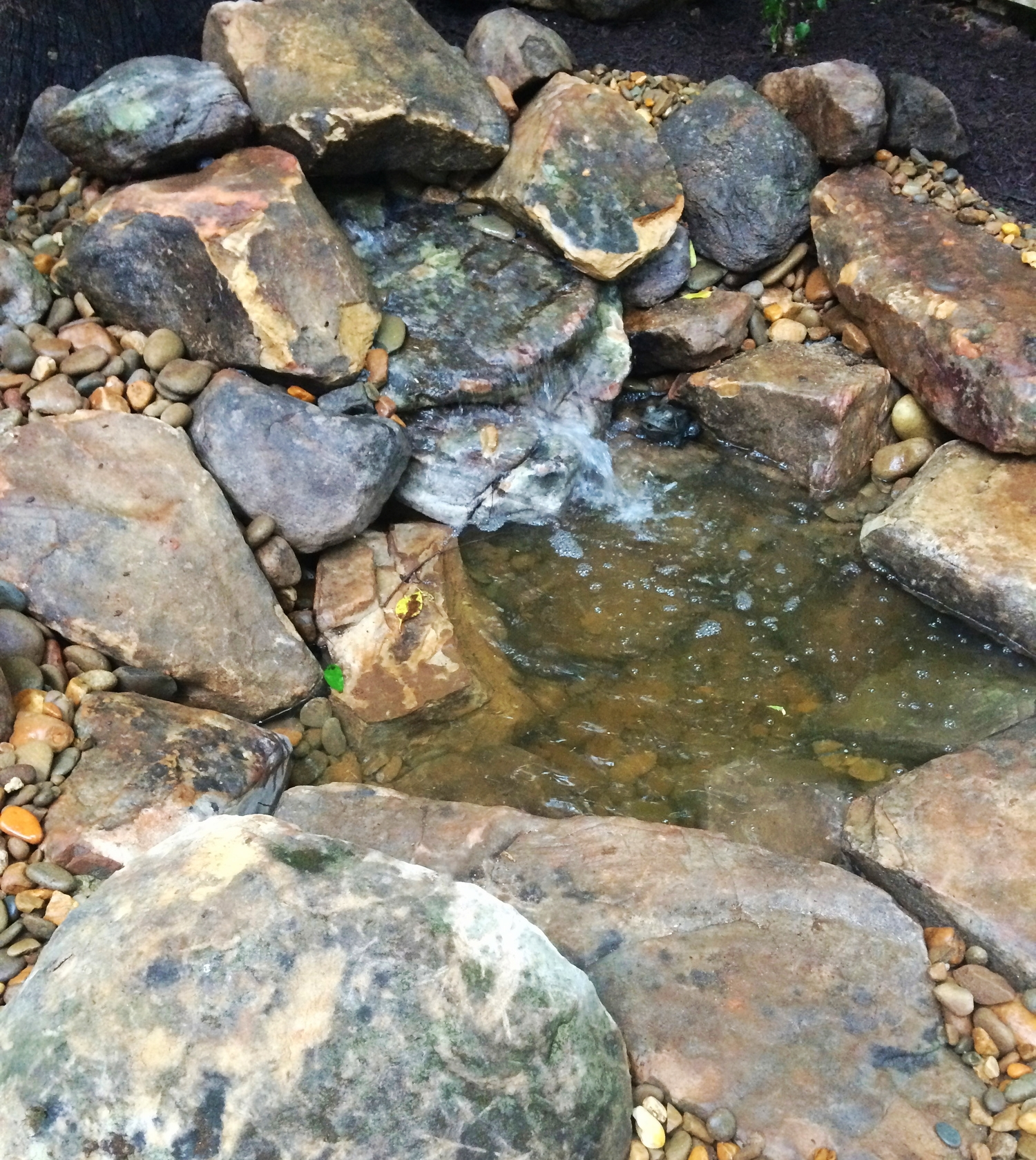 Low boulder and pebble water feature